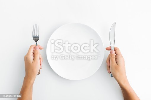 Dinner place setting. White empty plate and hand holding silver fork and spoon on white background, top view, copy space