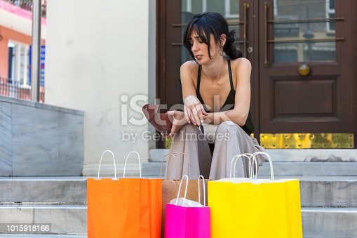 Black Friday, the face of a woman who has no money in her purse, shopping bags in front.
