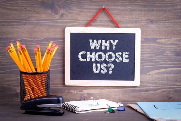 Warum wählen uns? Tafel auf einem hölzernen Hintergrund. – Foto