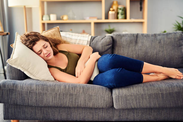 Why does it hurt so bad? Shot of a young woman suffering from stomach cramps on the sofa at home endometriosis stock pictures, royalty-free photos & images