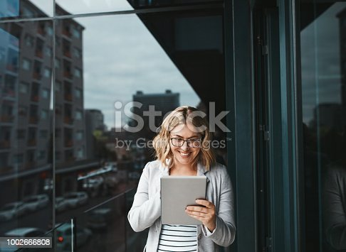 Shot of a young businesswoman using a digital tablet on the office balcony