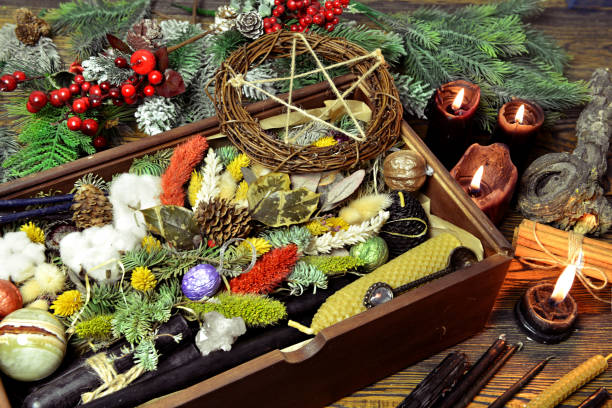 Wicca concept with box of presents, black candles, pentagram, magic healing herbs, conifer. stock photo