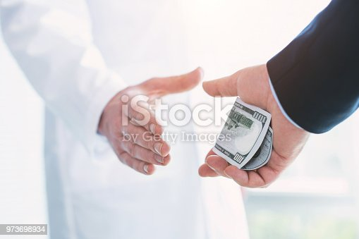 182362845 istock photo Wicked doctor taking a bribe for operation 973698934