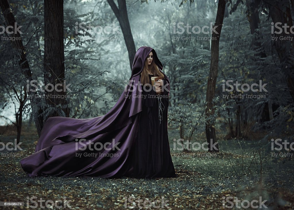Wicked witch in a long dark cloak wandering in woods stock photo