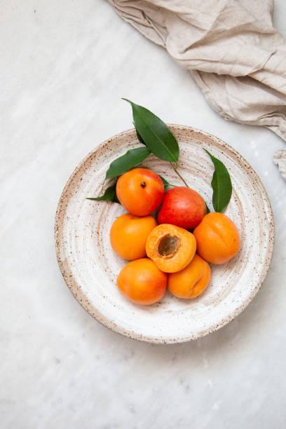 wicker korb aprikose auf marmornen hintergrund mit kopierraum und tageslicht - aprikose stock-fotos und bilder