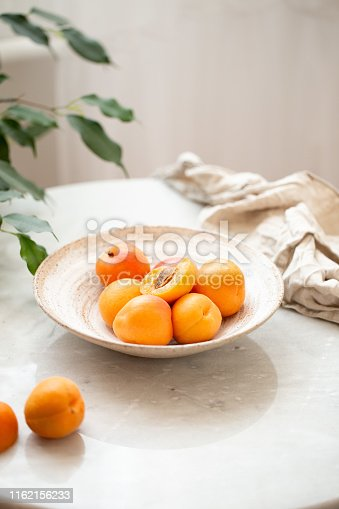 Wicker basket apricot on a marble background with copy space and daylight