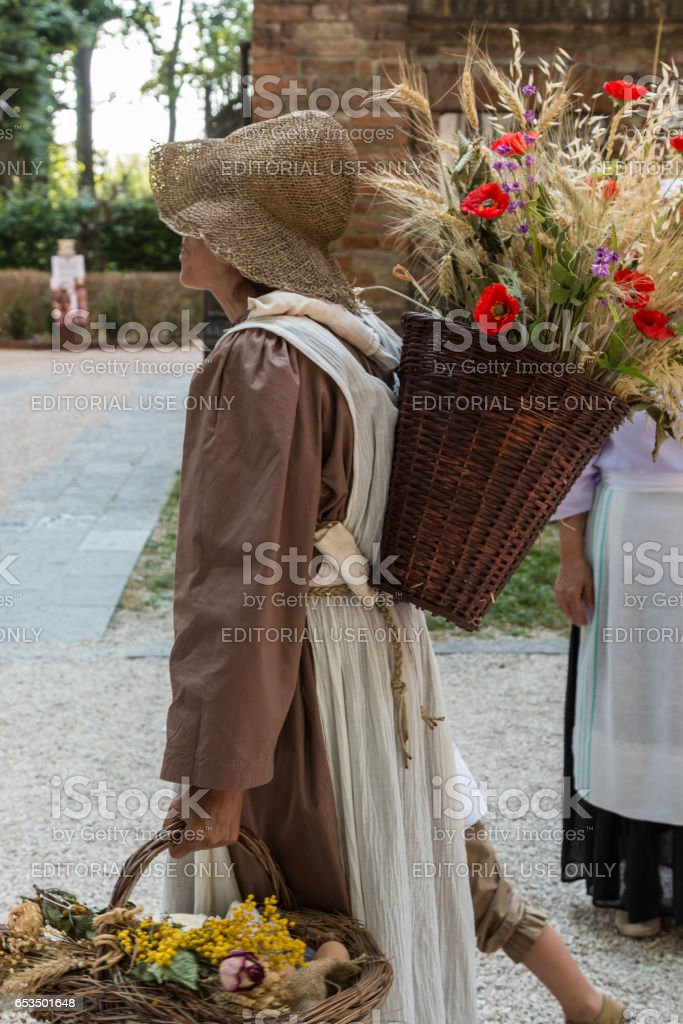 Parma, Italy - june 2015:Wicker Basket Filled with Sheafs of wheat and Red Flowers Carried over the Shoulder of Young Countrywoman stock photo