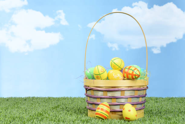 wicker basket full of colorful easter eggs stock photo