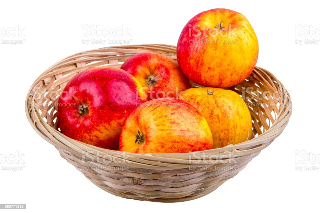 Wicker basket with apples on a white background stock photo