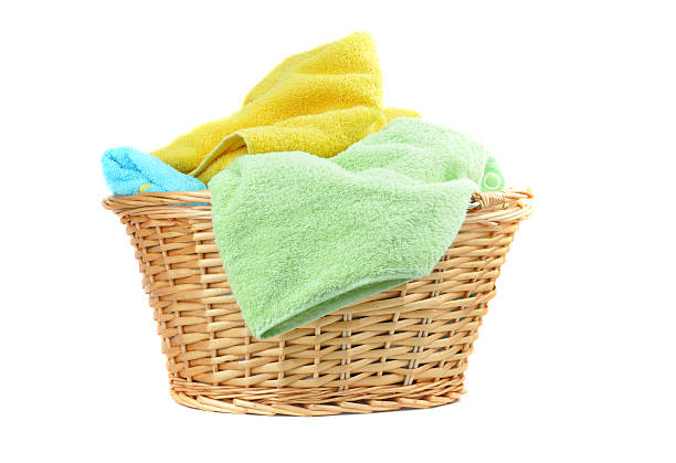 A wicker basket with colorful towels isolated on white Towels in a wicker basket, isolated on white laundry basket stock pictures, royalty-free photos & images