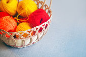 Wicker basket with needlework on table. Basket with colorful skeins of yarn, tangles, copy space