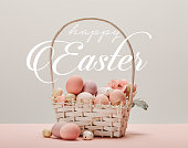 wicker basket with pink painted eggs, flowers and happy Easter white lettering on grey background
