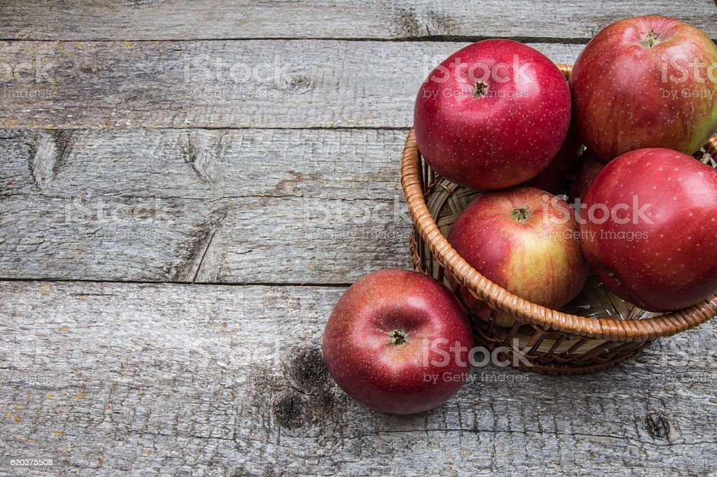 Wicker basket with red apples on wooden background zbiór zdjęć royalty-free