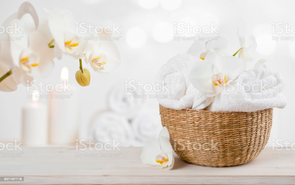 Wicker basket with spa towels on table over abstract background stock photo