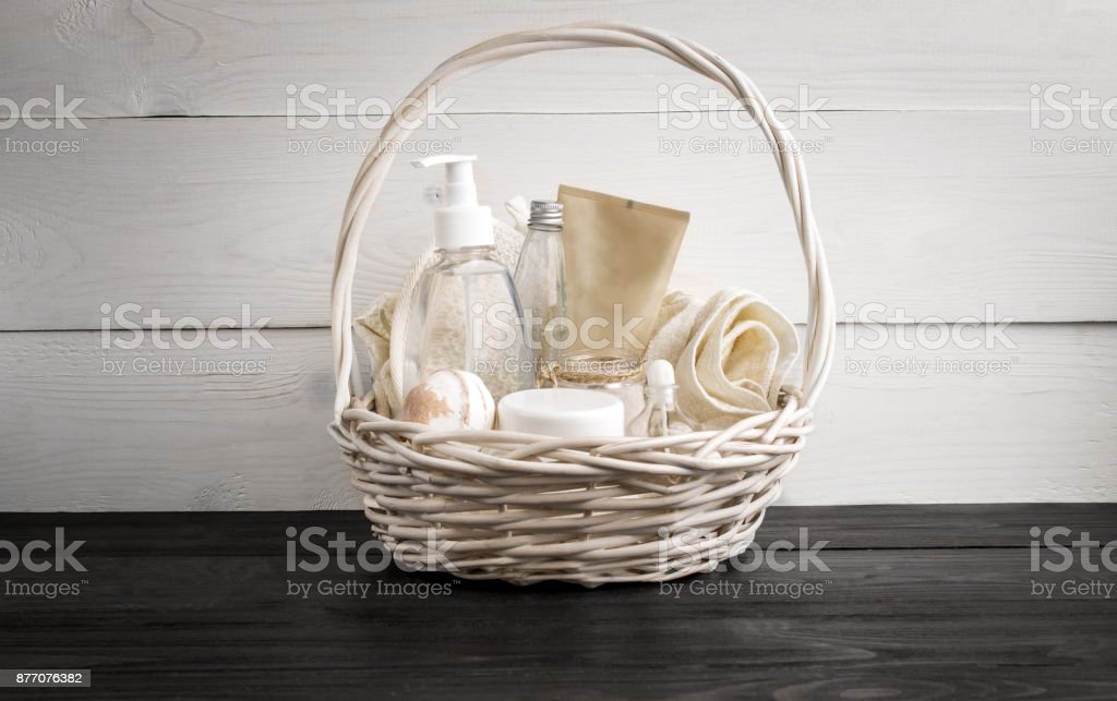 Wicker basket with spa treatments on table stock photo