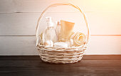 Wicker basket with spa treatments on table. Sun flare