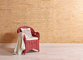 Decorative red and blue wicker chair and yellow brick wall decoration interior room concept.