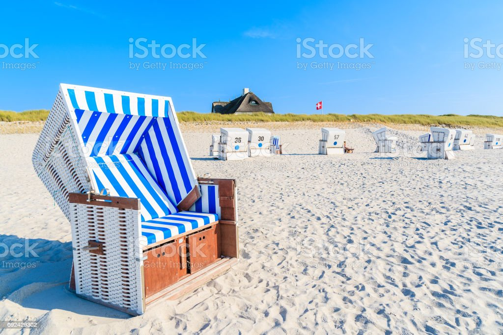 Wicker chairs on white sand Kampen beach with typical Frisian house roof in background, Sylt island, North Sea, Germany stock photo