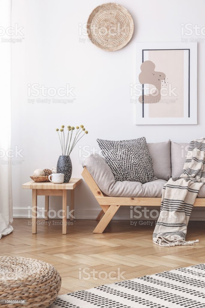 Wicker Decorations And A Painting On A White Wall Above A Wooden Sofa With Cushions In A Bright Living Room Interior Stock Photo Download Image Now Istock