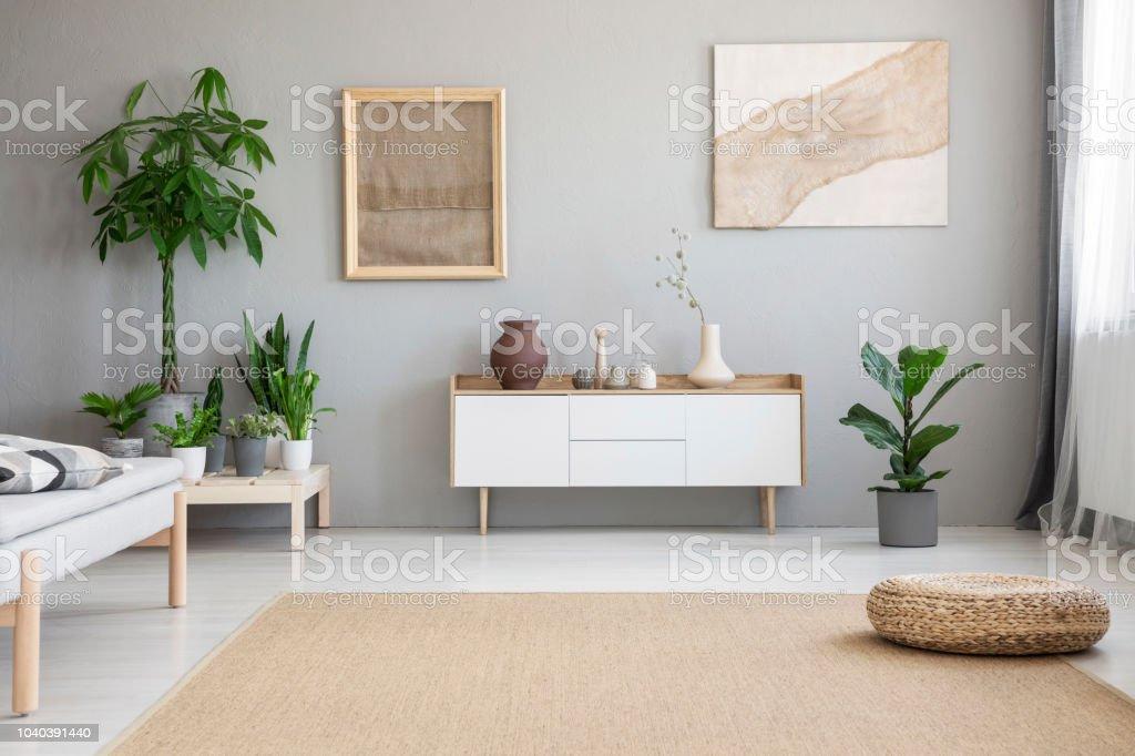Grote Plant Woonkamer : Rieten voetensteun geplaatst op grote tapijt op de vloer in echte