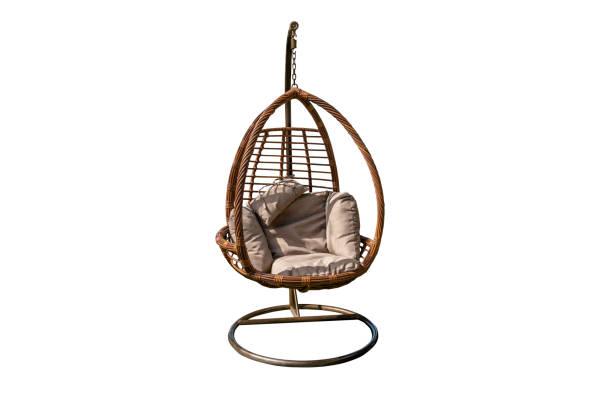 wicker opknoping stoel, swing opknoping op een ketting met orang kussens oranje kussen geïsoleerd op witte achtergrond met clipping path - schommelen bungelen stockfoto's en -beelden