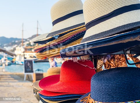 Wicker hats on the stand near the pier
