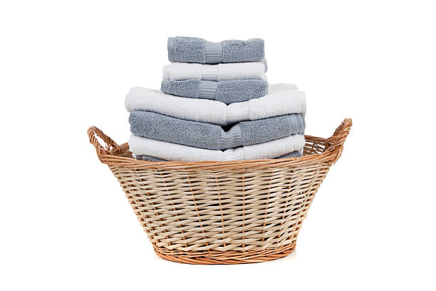 Wicker laundry basket full of white and gray towels A wicker laundry basket full of white and gray towels on a white background laundry basket stock pictures, royalty-free photos & images