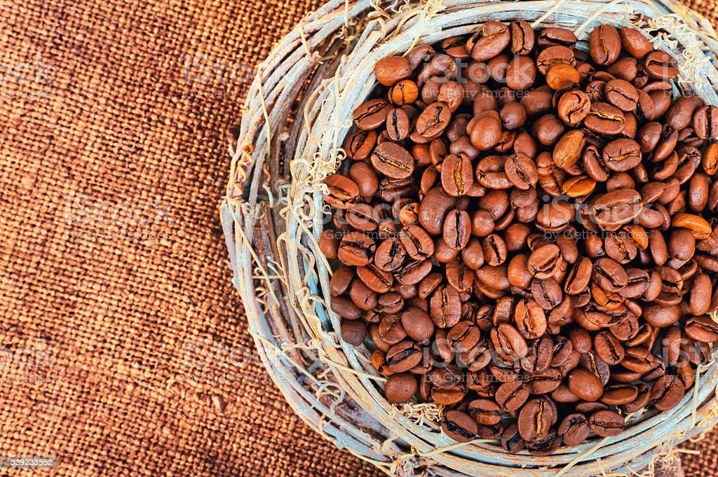 Wicker mug with coffee beans on a background of jute royalty-free stock photo