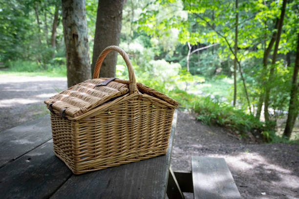Wicker picnic basket on picnic table stock photo