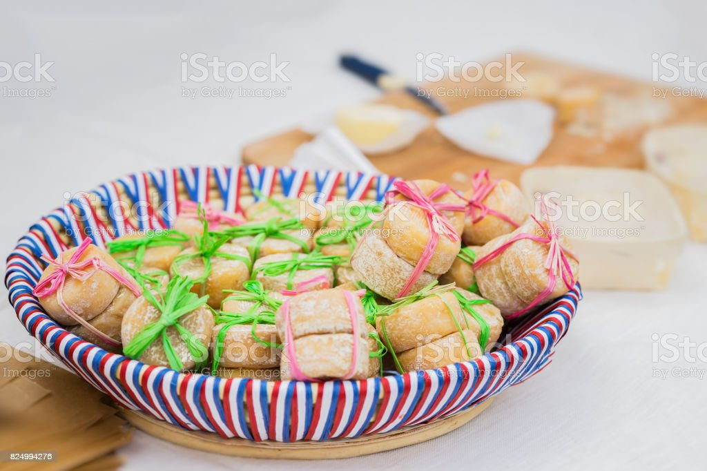 Wicker plate with the colors of the national flag with traditional organic small heads of french cheese, tied together, few pieces in market. Gastronomic products for gourme stock photo