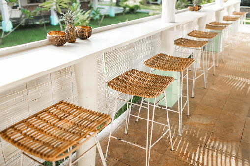 Wicker rattan chairs on bar counter. Trendy furniture design. Summer cafe terrace.