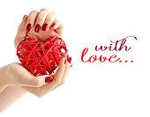 白い背景の上の女性の手で赤い籐心。赤いマニキュアで女の子の手で心をクローズ アップ。ハッピーバレンタインデー、愛の概念。