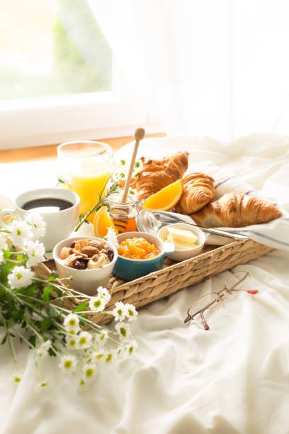 flüßleiner mit kontinentalem frühstück auf weißen bettwäsche - bett landhausstil stock-fotos und bilder