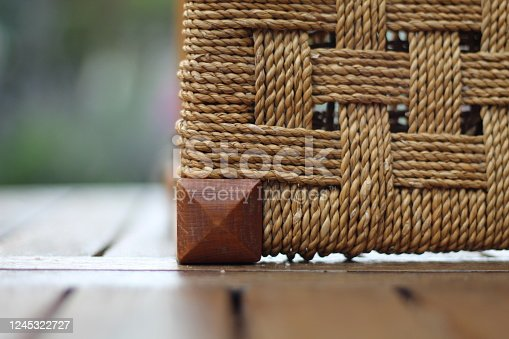 Wicker type effect of weaving on this stool lying on its side. Taken outside in the garden on the patio wooden table.