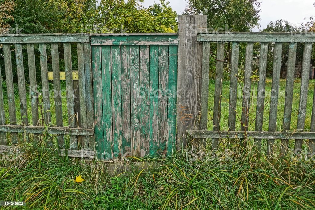 wicket on a gray wooden fence in green grass royalty-free stock photo
