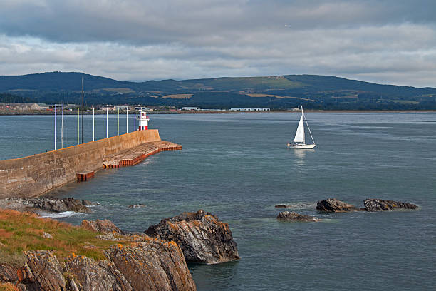 Wicklow Ireland Pier Breakwater Wall Lighthouse with sailboat stock photo