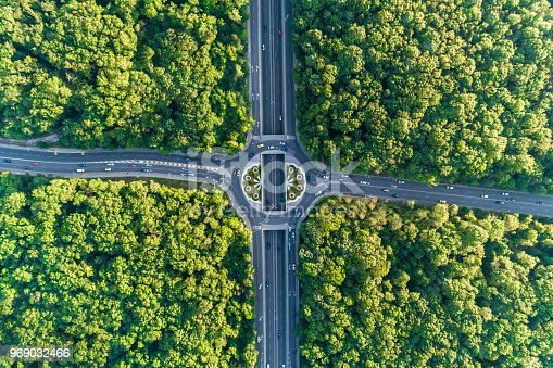 Time lapse aerial view looking down on traffic circle in the middle of a beautiful forest. The scene is situated in Sofia, the capital city of Bulgaria (Eastern Europe). The picture is taken with DJI Phantom 4 Pro video drone.