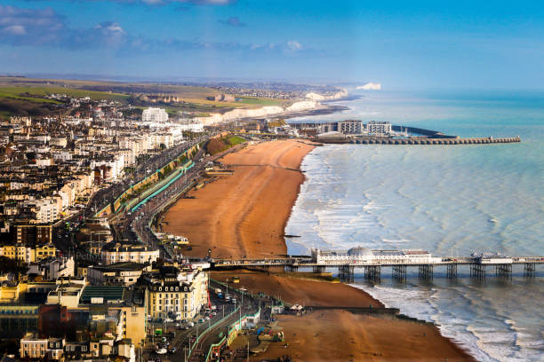 Wide angle aerial view of Brighton beach and coastline, Brighton, UK Wide angle aerial view of the beach and coastal town of Brighton, East Sussex, UK. We can see both piers extending out into the sea and in the distance the white cliffs of Sussex. Horizontal colour image with copy space. southeast england stock pictures, royalty-free photos & images