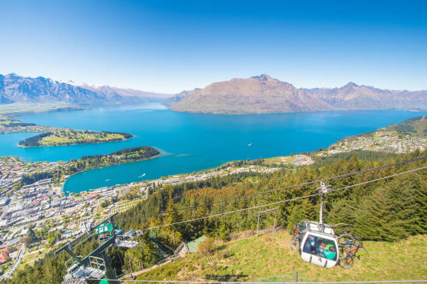 Wide angle cable car going above Queenstown and Lake Wakatipu in the Remarkable Mountains of New Zealand over residence area stock photo