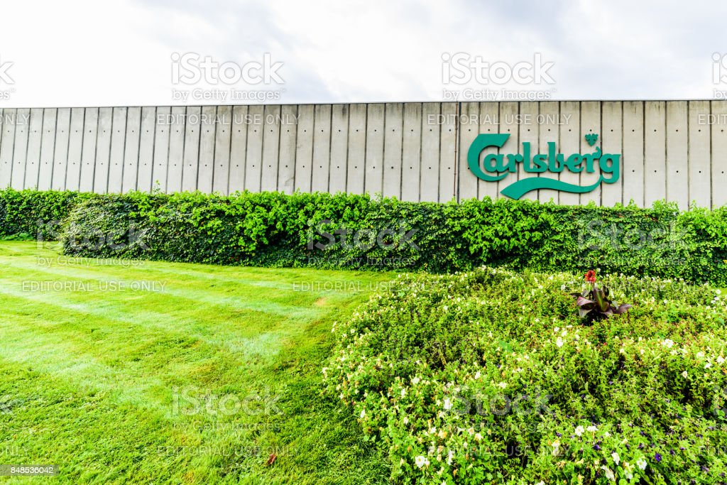 Wide angle daylight view of Carslberg logo on factory fence stock photo