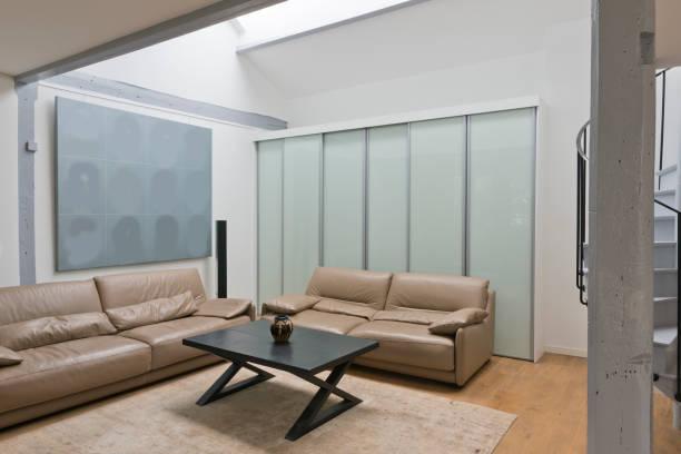 weitwinkel von wohnraum und küche mit wendeltreppe. - sofa u form stock-fotos und bilder