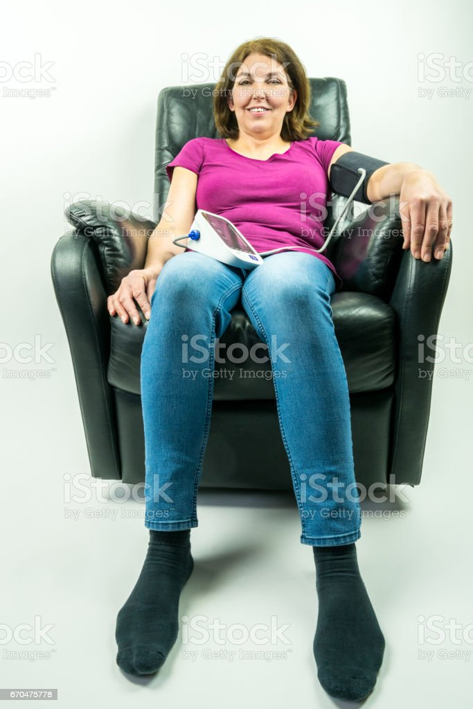 Wide angle of pretty middle-age woman sitting in black leather recliner armchair. Checking blood pressure using portable blood pressure machine. royalty-free stock photo