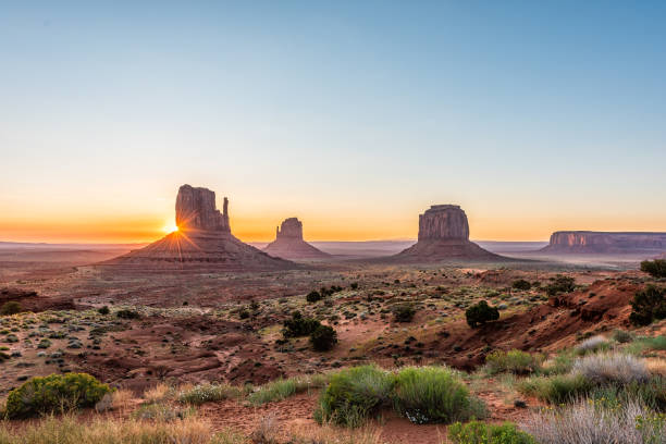 Wide angle overlook panoramic view of buttes and horizon in Monument Valley at sunrise colorful light and sunburst in Arizona with orange rocks stock photo
