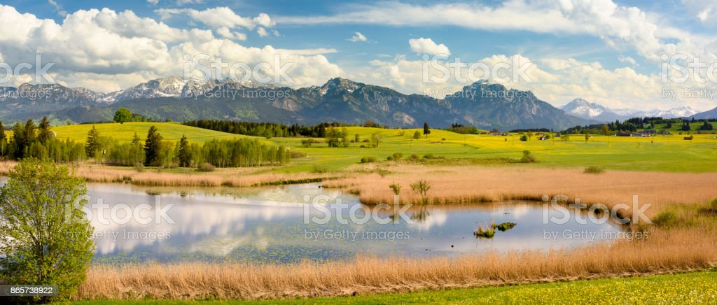 wide angle panorama landscape in Bavaria with lake and alps mountains stock photo