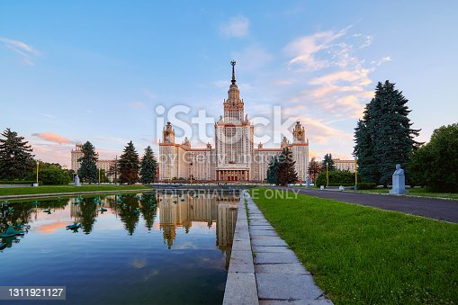 Moscow, Russia - May 9 2020: Wide angle panoramic view of sunset campus of Moscow university  under dramatic sky in spring with water reflections