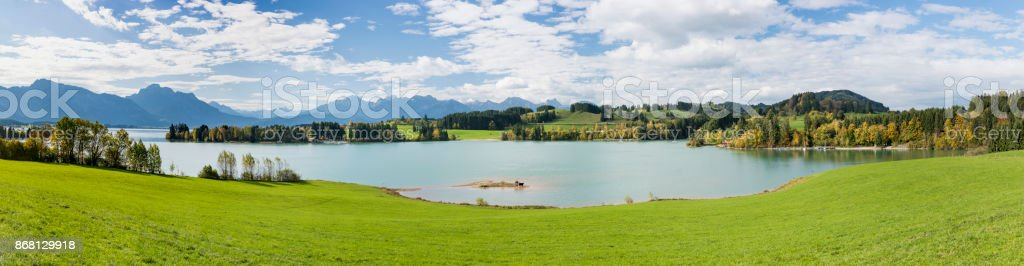 wide angle panoramic view to rural landscape in Bavaria with alps mountains and lake Forggensee stock photo