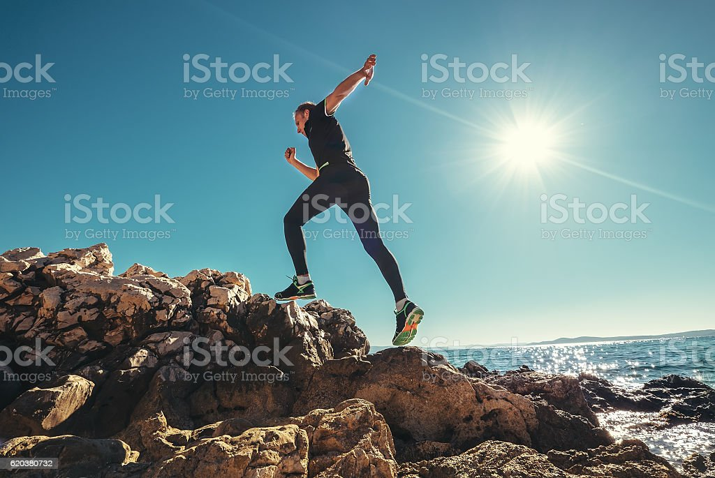 Wide angle photo of Man Running by the Rocky seaside foto de stock royalty-free