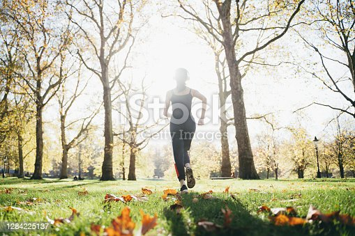 istock Wide angle shot of a young Asian woman running in the park 1284225137