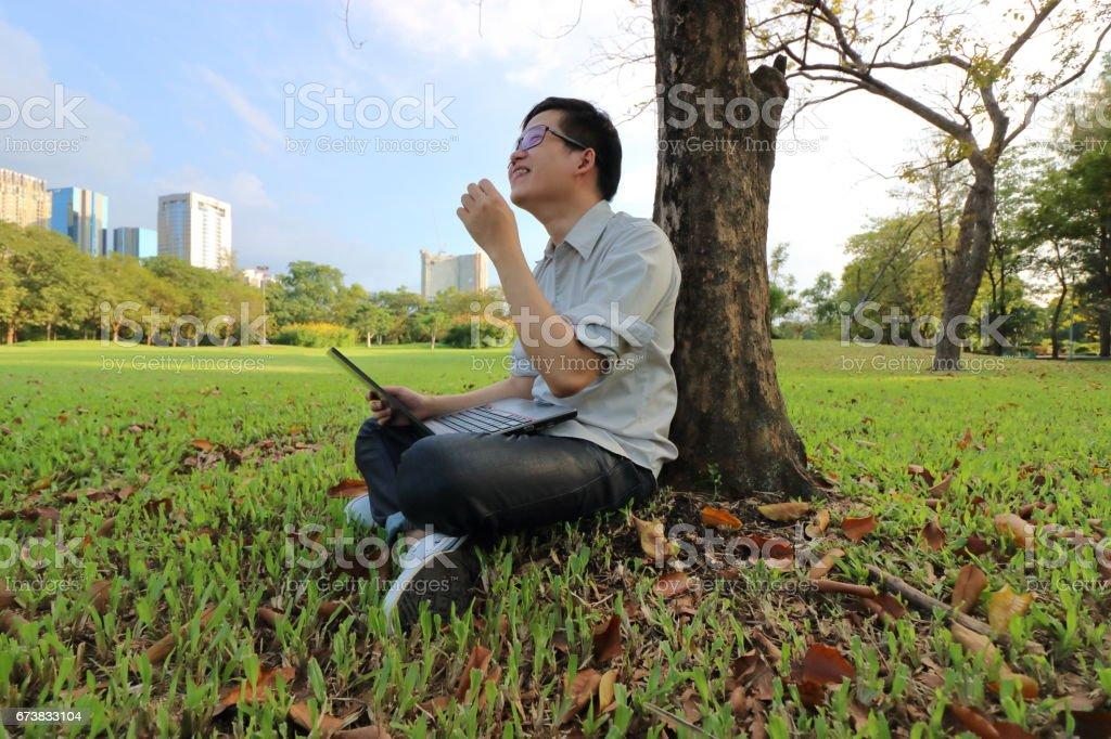 Prise de vue grand angle de gai jeune homme est en riant avec un ordinateur portable dans le parc de la ville. photo libre de droits