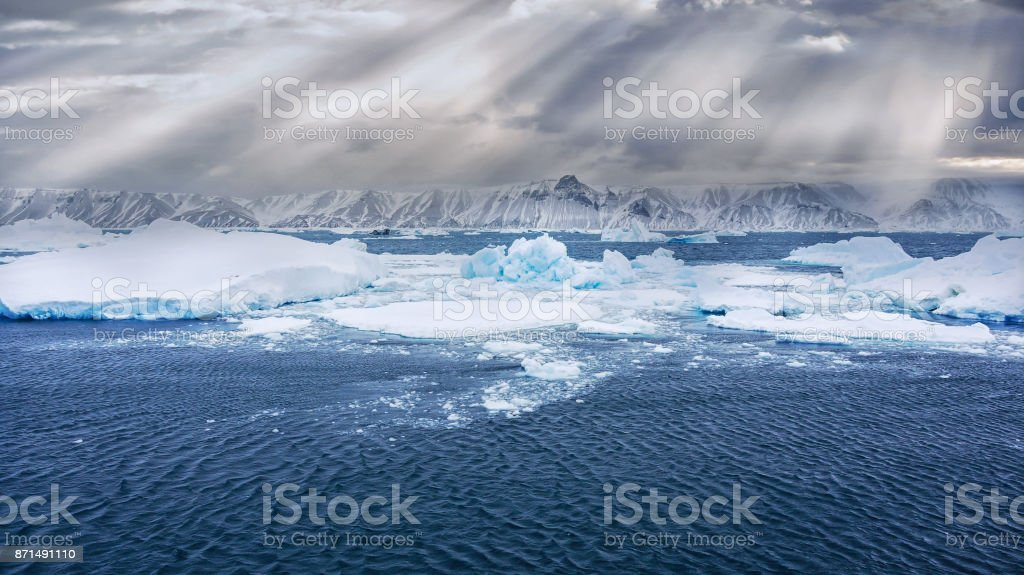 Wide angle view from the sea of an Antarctica landscape, with floating icebergs and growlers, and Snow Hill Island in the background, with its snowcapped mountains and sunbeams in the background. stock photo